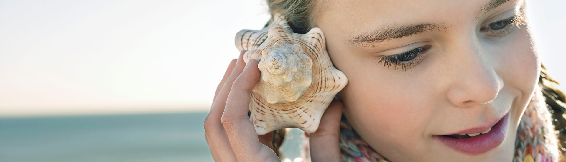 blonde girl listening to a seashell on a beach